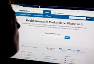 A woman looks at the HealthCare.gov insurance exchange …