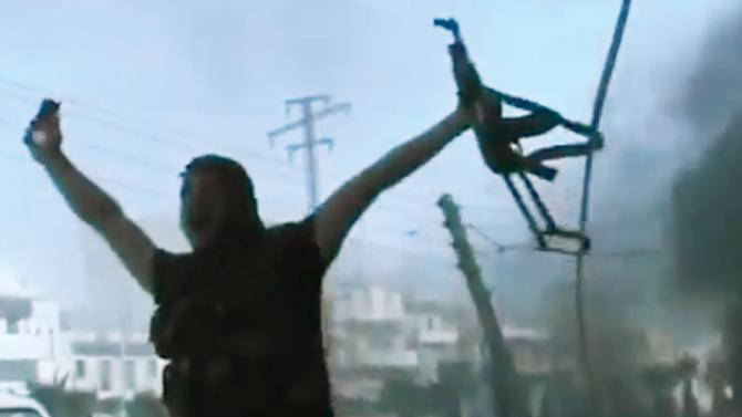 In this image made from amateur video released by the Ugarit News and accessed Monday, July 23, 2012, a Free Syrian Army soldier reacts during clashes with Syrian government troops in Aleppo, Syria. The Syrian regime acknowledged for the first time Monday that it possessed stockpiles of chemical and biological weapons and said it will only use them in case of a foreign attack and never internally against its own citizens. (AP Photo/Ugarit News via AP video) TV OUT, THE ASSOCIATED PRESS CANNOT INDEPENDENTLY VERIFY THE CONTENT, DATE, LOCATION OR AUTHENTICITY OF THIS MATERIAL