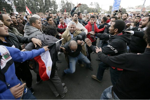 Egyptian President Mohammed Morsi's supporters beat an opponent, center, during clashes outside the presidential palace, in Cairo, Egypt, Wednesday, Dec. 5, 2012. Wednesday's clashes began when thousa