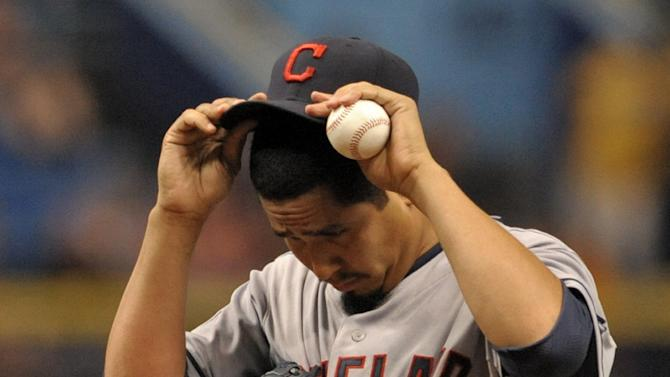 Cleveland Indians starter Carlos Carrasco adjusts his cap between pitches during the fifth inning of a baseball game against the Tampa Bay Rays Wednesday, July 1, 2015, in St. Petersburg, Fla. (AP Photo/Steve Nesius)