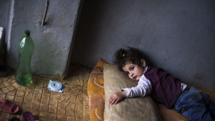 Rada Hallabi, 4, who is sick with diabetes, lies on a blanket in a refugee camp on the border with Turkey, near Azaz village, Syria, Sunday, Sept. 30, 2012. (AP Photo / Manu Brabo)