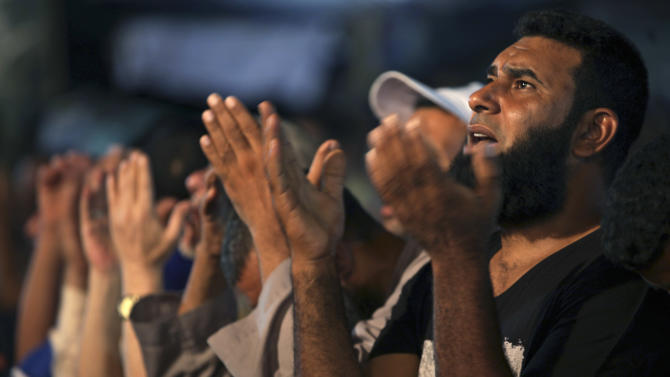 Supporters of Egypt's ousted President Mohammed Morsi pray outside Rabaah al-Adawiya mosque, where protesters have installed a camp and hold daily rallies at Nasr City in Cairo, Egypt, Sunday, Aug. 4, 2013. (AP Photo/Khalil Hamra)