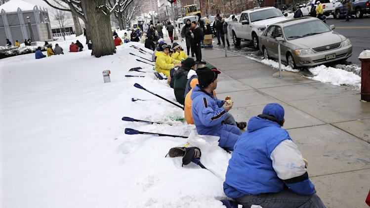 "Workers take a lunch break from shoveling snow near the Statehouse in Tuesday, Feb. 18, 2014, in Trenton, N.J., after a quick-moving storm brought several inches of snow as well as rare ""thundersnow"" to parts of the winter-weary East Coast. (AP Photo/Mel Evans)"