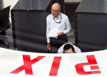 Employees look at monitors at the Tokyo Stock Exchange in Tokyo