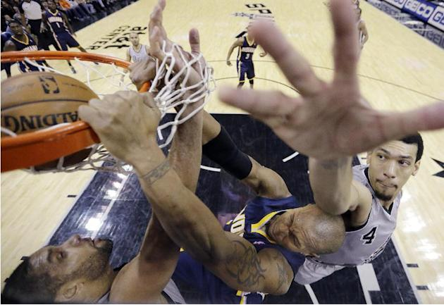 Indiana Pacers' David West, center, scores with a dunk over San Antonio Spurs' Tim Duncan, left, and Danny Green, right, during the second half of an NBA basketball game, Saturday, Dec. 7, 201