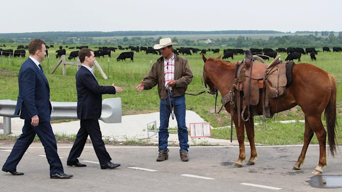 Russian Prime Minister Dmitry Medvedev, second left, shakes hands with a farmer as he visits  cattle breeding farm Kotlyakovo in Bryansk region, 380 km (238 miles) southwest of Moscow, Russia,  Wednesday, May 23, 2012. (AP Photo/RIA-Novosti, Yekaterina Shtukina, Presidential Press Service).