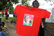 A street vendor in Accra hawks T-shirts showing late President John Atta Mills. Ghana began three days of funeral rites for Mills on Wednesday, with his body to lie in state ahead of his burial to be attended by foreign dignitaries including Hillary Clinton.
