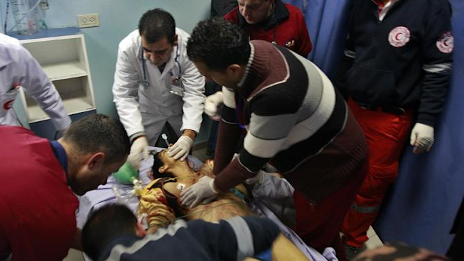 Palestinian doctors attempt to save the life of a Palestinian man, identified by relatives as Samir Awad, at the Ramallah hospital, Tuesday, Jan 15, 2013. Awad died from wounds. Palestinians say the Israeli military has shot dead the 17-year-old Palestinian boy near the West Bank separation barrier. (AP Photo/Majdi Mohammed)