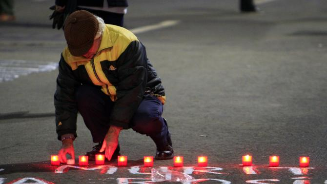 A man places candles on the pavement during the 25th anniversary of the country's 1989 revolution in central Bucharest