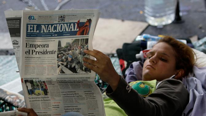 """A student protestor demanding more information about President Hugo Chavez's health reads a newspaper with a front page headline that reads in Spanish; """"The President worsens,"""" in Caracas, Venezuela, Tuesday, March 5, 2013.  A brief statement read on national television by Communications Minister Ernesto Villegas late Monday carried the sobering news about the charismatic 58-year-old leader's deteriorating health. Villegas said Chavez is suffering from """"a new, severe infection."""" The state news agency identified it as respiratory. (AP Photo/Fernando Llano)"""