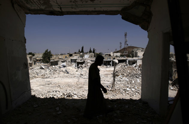 A Syrian man walks in his house which was destroyed in a Syrian government forces shelling, over looking the rubble of other houses, in Azaz, on the outskirts of Aleppo, Syria, Wednesday, Aug. 29, 2012. (AP Photo/Muhammed Muheisen)