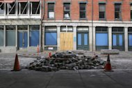 In this Thursday, Feb. 7, 2013 photo, cobblestones are piled up on Front St. in New York outside the shuttered J. Crew store. Nearly four months after Superstorm Sandy hit, the historic cobblestone streets near the water&#39;s edge in lower Manhattan are eerily deserted, and among local business owners, there is a pervasive sense that their plight has been ignored by the rest of Manhattan. (AP Photo/Mary Altaffer)