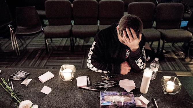 """Marysville Pilchuck High School freshman, Cameron Moody, 14, silently prayed amidst candles and Kleenex at a vigil within The Grove Church in mourning of an earlier shooting at his school that left two dead and four wounded Friday, Oct. 24, 2014, in Marysville, Washington. Less than one full quarter into high school, Moody was stunned. """"I'm not going to be able to walk into the cafeteria the same way,"""" Moody said. """"This is going to change everything for me."""" Several students identified the shooter as Jaylen Fryberg. Providence Regional Medical Center in Everett took in the wounded. (AP Photo/seattlepi.com, Jordan Stead)"""