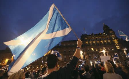'Yes' campaigners holding Scottish Saltire flags gather for a rally in George Square, Glasgow