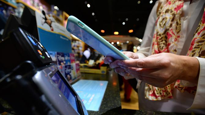 IMAGE DISTRIBUTED FOR DISNEY STORE - The magic of Apple Pay comes to Disney Store. A guest makes a purchase at a Disney Store in Glendale, CA using the new Apple Pay technology, which brings an easy, secure and private way to make payments. The new technology rolled out to Disney Store locations nationwide on Monday, October 20, with the launch of Apple's iOS 8.1 software update. (Photo by Jordan Strauss/Invision for Disney Store/AP Images)