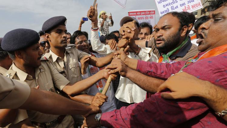 Supporters of India's Congress party scuffle with police during a protest against what they say is a rise in the prices of essential food items, in Ahmedabad