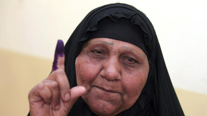 An Iraqi woman displays her ink-stained finger after voting at a polling center during the country's provincial elections in Baghdad, Iraq, Saturday, April 20, 2013. Polls opened amid tight security in Iraq on Saturday for regional elections in the country's first vote since the U.S. military withdrawal, marking an important test of the country's stability. (AP Photo/Karim Kadim)