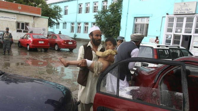 An Afghan man carries an injured child, a victim of a suicide explosion in the central province of Ghazni, Afghanistan Saturday, June 11, 2011. A suicide bomber, pushing an ice cream cart, exploded killing one child and injuring three more in the central province of Ghazni, according to provincial police chief Mohammad Hussain. A string of attacks across Afghanistan killed at least 21 people Saturday, officials said, while the U.N. released a report showing May to be the deadliest month for Afghan civilians since 2007. (AP Photo/Rahmatullah Nikzad)