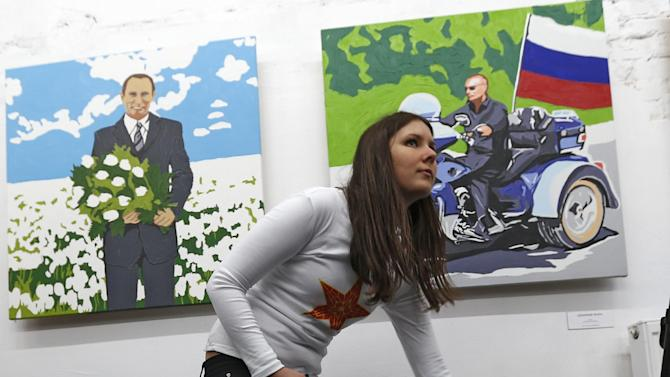 """A lady with a dog stands in front of the paintings by artist Alexei Sergiyenko during the opening of his exhibition """"President. The kindest person"""" devoted to the 60th birthday of Russian President Vladimir Putin at the Flacon design workshop in Moscow, Sunday Oct. 7, 2012. Vladimir Putin turns 60-years old on Sunday, Oct. 7, 2012, and has recently sought to demonstrate his youthful vigor by many personal endeavors, but while he has shown creativity in his action-man stunts, the Russian president seems surprisingly vulnerable to the vagaries of oil prices. (AP Photo/Sergey Ponomarev)"""
