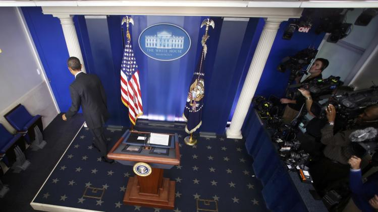 U.S. President Obama gestures departs a year-end news conference in the White House briefing room in Washington