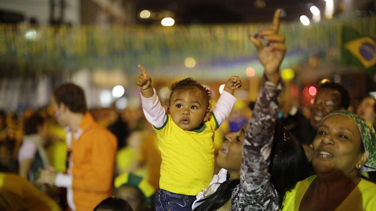 Brazilians soccer fans of all ages, cheer after Brazil scored against Cameroon while watching the match on a giant television screen in Bixiga neighborhood in Sao Paulo, Brazil, Monday, June 23, 2014. Brazil's Neymar scored twice in the first half to lead Brazil to a 4-1 win over Cameroon on Monday, helping the hosts secure a spot in the second round of the soccer World Cup