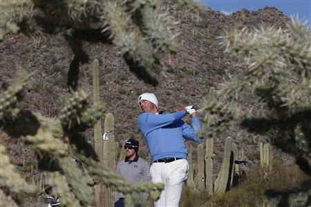Kuchar of the U.S. tees off on the 16th hole as Mahan of the U.S. watches in the background during the championship match of the WGC-Accenture Match Play Championship golf tournament in Marana