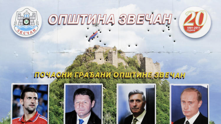 In this photo taken Friday, March 29, 2013, a billboard damaged with bullet holes shows honorary citizens of Zvecan, from left, tennis player Novak Djokovic, Dr. Zoran Krivokapic, politician Jugoslav Kostic and Russian President Vladimir Putin, on a road near Zvecan northern Kosovo. Mitrovica, a former mining center in northern Kosovo, was sharply split into Serb and Albanian parts at the end of the Kosovo war in 1999. The town's fate has come into renewed focus as officials from Serbia and Kosovo meet in Brussels on Tuesday in hopes of reaching an agreement that could pave the way for reuniting the divided city. (AP Photo/Darko Vojinovic)