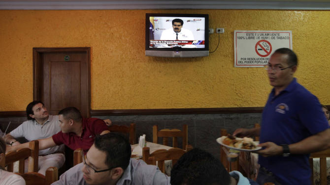 People sit in a restaurant where a TV on the wall shows a live image of Venezuela's Vice President Nicolas Maduro addressing the nation on state television during a government meeting in Caracas, Venezuela, Tuesday, March 5, 2013. Maduro met with top Venezuelan government ministers, the military high command and all 20 loyalist governors in Caracas following word of President Hugo Chavez's deteriorating health. (AP Photo/Ariana Cubillos)