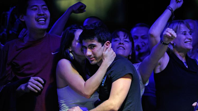 Jesse Sylvia, of West Tisbury, Mass., gets a hug from his girlfriend, Ashley Sleeth, left, after winning a hand during day seven of the Main Event at the 43rd annual World Series of Poker on Monday, July 16, 2012, in Las Vegas. (AP Photo/David Becker)