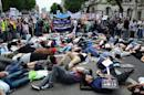 Protesters lie-down as they take part in demonstration against Israeli airstrikes in Gaza, during a rally in central London, on July 19, 2014