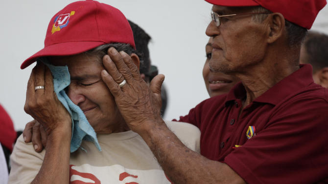 A supporter of Venezuela's late President Hugo Chavez cries outside the military museum where Chavez's body is being transferred to in Caracas, Venezuela, Friday, March 15, 2013.  Chavez's body is being transferred from the military academy where it has been lying in state to the military museum that will serve as his final resting place. Chavez was 58 when he died of an undisclosed type of cancer on March 5. (AP Photo/Ariana Cubillos)