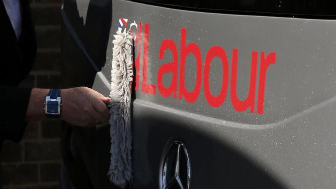 The driver cleans the front of Britain's Labour Party leader Ed Miliband's battle bus at a campaign event in Pensby northern England