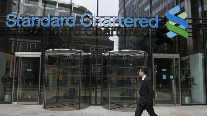 FILE - In this Aug. 7, 2012 file photo, a man walks past the headquarters of Standard Chartered bank in London. Benjamin Lawsky, New York's superintendent of financial services, said Tuesday, Aug. 14, 2012, that his agency has reached a $340 million settlement with Standard Chartered Bank to resolve an investigation into whether the British bank schemed with the Iranian government to launder $250 billion from 2001 to 2007. (AP Photo/Sang Tan, File)