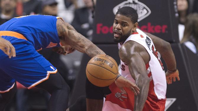 Toronto Raptors forward Amir Johnson, right, is knocked down by New York Knicks J.R. Smith, left, during first half NBA basketball action in Toronto on Friday, March 22, 2013. (AP Photo/The Canadian Press, Nathan Denette)