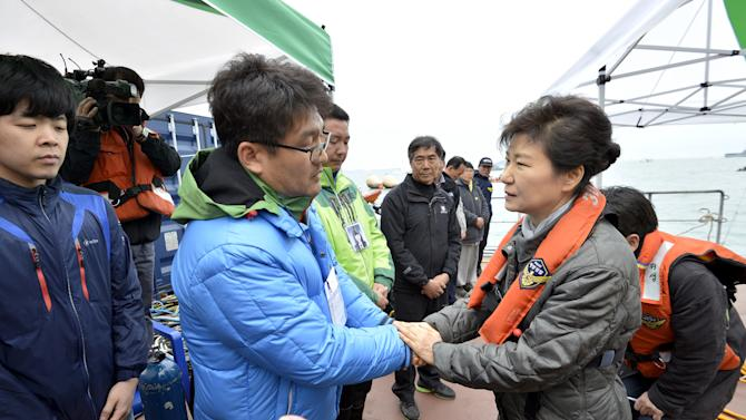 South Korean President Park Geun-hye, right, consoles a relative of a passenger aboard the sunken Sewol ferry at the site where the ship sank in waters off the southern coast near Jindo, South Korea, Sunday, May 4, 2014. Park told families of those missing in the sunken ferry that her heart breaks knowing what they are going through, as divers recovered two more bodies on Sunday. (AP Photo/Yonhap) KOREA OUT
