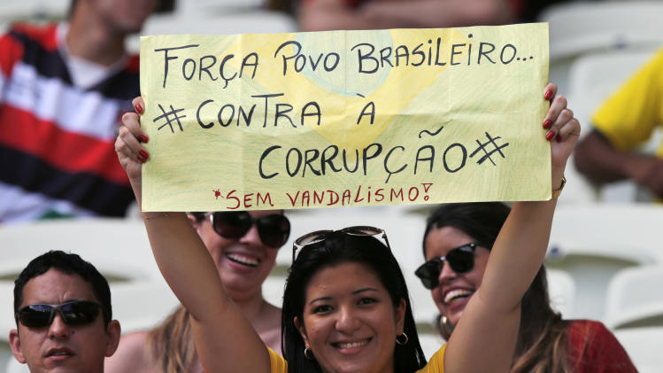 """A spectator holds a sign """"Be strong Brazilian people - against corruption - without vandalism"""" prior to the soccer Confederations Cup group B match between Nigeria and Spain at the Castelao stadium in Fortaleza, Brazil, Sunday, June 23, 2013. (AP Photo/Fernando Llano)"""