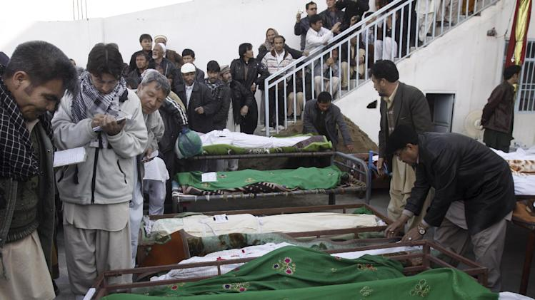 Pakistanis gather by the lifeless bodies of Saturday's bombing victims, in a mosque in Quetta, Pakistan, Sunday, Feb. 17, 2013. Angry residents on Sunday demanded government protection from an onslaught of attacks against Shiite Muslims, a day after scores of people were killed in a massive bombing that a local official said was a sign that security agencies were too scared to do their jobs. (AP Photo/Arshad Butt)