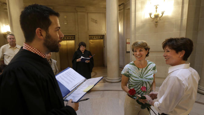 """Marriage commissioner Jared Scherer, left, officiates as Pam Shaheen, center, marries Mary Beth Gabriel at City Hall in San Francisco, Friday, June 28, 2013. A three-judge panel of the 9th U.S. Circuit Court of Appeals issued a brief order Friday afternoon dissolving, """"effective immediately,"""" a stay it imposed on gay marriages while the lawsuit challenging the ban advanced through the courts. (AP Photo/Jeff Chiu)"""