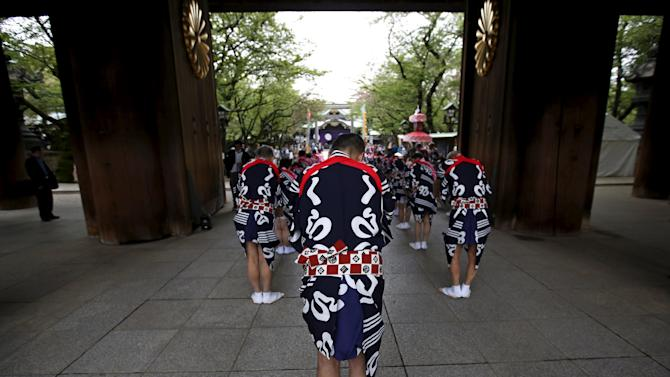 Traditional dance group members in costumes bow towards the main shrine as they visit Yasukuni Shrine in Tokyo