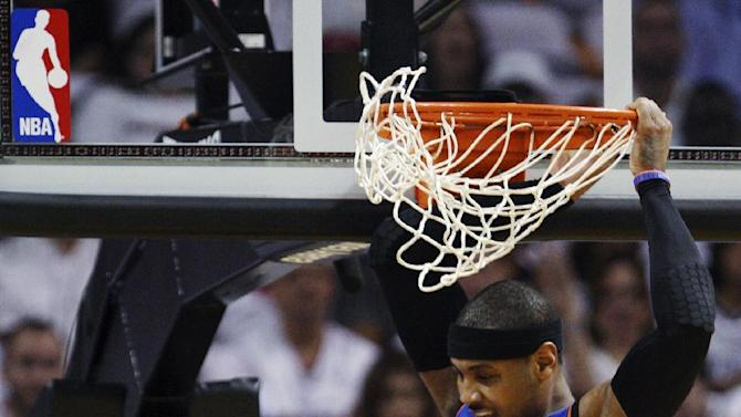New York Knicks forward Carmelo Anthony (7) comes down after dunking over Miami Heat guard Dwyane Wade during the first half of an NBA basketball game in the first round of the Eastern Conference playoffs, Wednesday, May 9, 2012, in Miami. (AP Photo/Wilfredo Lee)