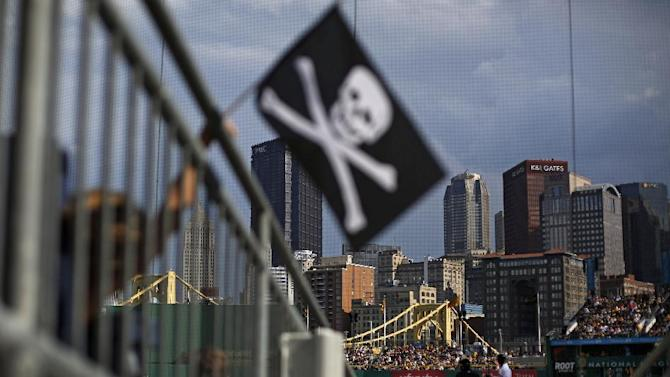 A Pittsburgh Pirates fan in the seats behind home plate holds a Jolly Roger during the ninth inning of a baseball game between the Pirates and the Milwaukee Brewers in Pittsburgh, Sunday, Sept. 21, 2014. The Pirates won 1-0. (AP Photo/Gene J. Puskar)