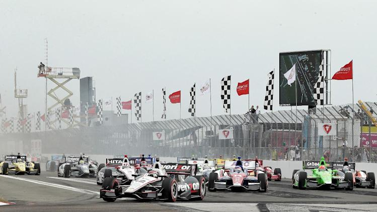 Will Power, of Australia, (12) leads the field at the start of the IndyCar series Honda Grand Prix of St. Petersburg auto race Sunday, March 24, 2013, in St. Petersburg, Fla. (AP Photo/Chris O'Meara)