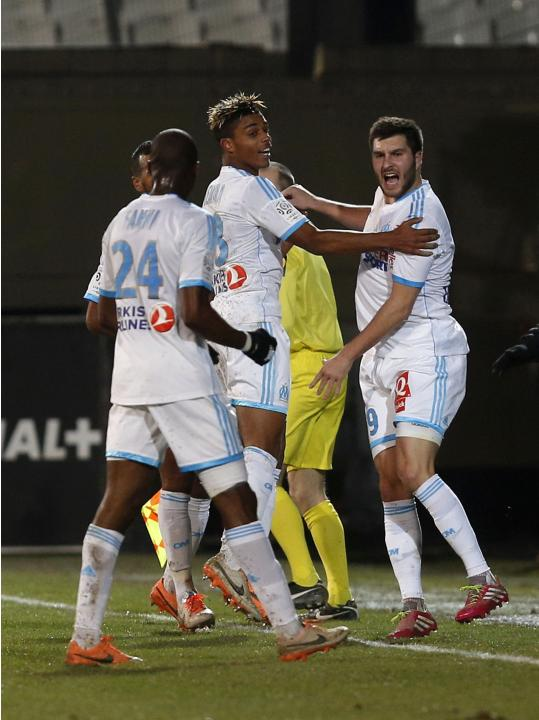 Olympique Marseille's Andre-Pierre Gignac celebrates his goal against Valenciennes with teammates Mario Lemina and Rod Fanni during their French Ligue 1 soccer match at the Velodrome Stadium in Ma