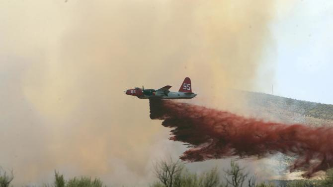FILE - In this file photo made July 13, 2006, a P2-V Neptune air tanker drops retardant on a wildfire southwest of Elko, Nev. An air tanker dropping retardant on a remote wildfire along the Utah-Nevada line crashed Sunday, June 3, 2012, killing both crew members, authorities said. The pilots were flying a P-2V air tanker that is owned by Neptune Aviation Services of Missoula, Mont. (AP Photo/Elko Daily Free Press, Ross Andreson, file)