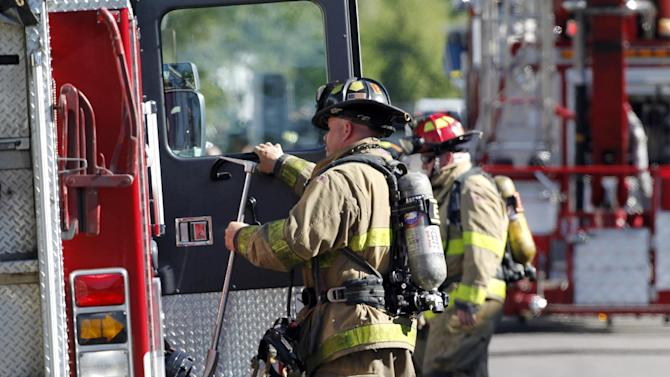 """Firefighters standby outside the apartment of James Holmes in Aurora, Colo., Saturday, July 21, 2012.  Federal authorities detonated one small explosive and disarmed another inside Holmes' apartment, but several other explosive devices remained, said Aurora police Sgt. Cassidee Carlson. Twelve people were killed and dozens were injured in a shooting attack early Friday at a packed movie theater during a showing of the Batman movie, """"The Dark Knight Rises.""""   Police have identified Holmes, 24, as the suspected shooter. (AP Photo/Ed Andrieski)"""