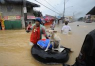 A resident pushes an improvised inflatable boat loaded with his dog through flood waters as they head for a safer area in the village of Tumana, Marikina town, in suburban Manila, after torrential rains inundated most of the capital