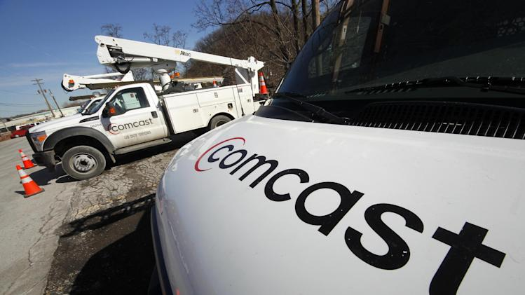 FILE - In a Feb. 15, 2011 file photo, Comcast logos are displayed on installation trucks in Pittsburgh. Comcast Corp., the country's largest cable company, reported Wednesday May 2, 2012, a 30 percent profit increase in the first quarter, beating expectations on the strength of Super Bowl advertising and its popular broadband service.   (AP Photo/Gene J. Puskar, file)
