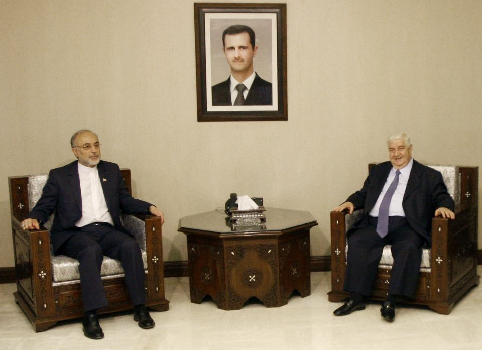 Iranian Foreign Minister Ali Akbar Salehi, left, meets with Syrian Foreign Minister Walid Moallem, in Damascus, Syria, Wednesday, Sept. 19, 2012. The portrait of Syrian President Bashar Assad is seen top center.(AP Photo/Muzaffar Salman)