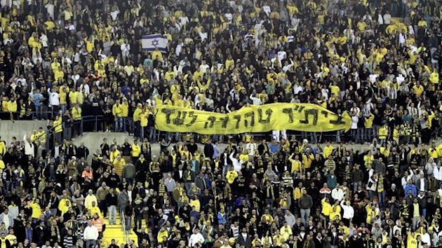 Beitar Jerusalem fans hold up anti-Arab banners during an Irsaeli league match. Fans of the club are notoriously right-wing and object to the signing of Arab or Muslim players