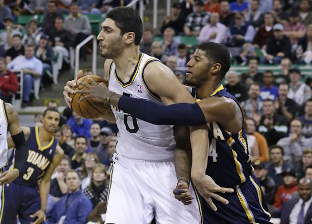 Indiana Pacers' Paul George (24) and Utah Jazz's Enes Kanter (0) battle for a rebound in the fourth quarter during an NBA basketball game Wednesday, Dec. 4, 2013, in Salt Lake City.  The India